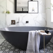 A honed bluestone freestanding tub adds a modern