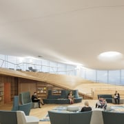 The library building is extremely energy efficient, with architecture, building, ceiling, daylighting, design, floor, flooring, furniture, home, house, interior design, living room, real estate, roof, room, shade, table, gray
