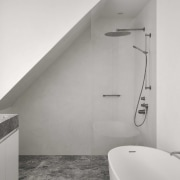 A clever shower stall sits tucked under the