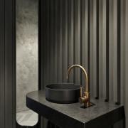 A batten wall, black benchtop basin, brass mixer
