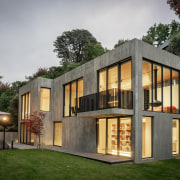 At night, the substantial glazing turns the home
