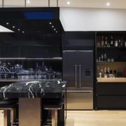 A suspended bulkhead over the island utilises the cabinetry, countertop, interior design, kitchen, black