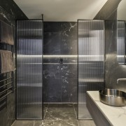The ensuite has a dark and moody atmosphere,