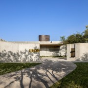 The architects describe the lodge as having an architecture, building, concrete, daytime, design, estate, facade, grass, home, house, land lot, landscape, landscaping, plant, property, real estate, residential area, sky, stone wall, tree, villa, wall, yard, teal, gray