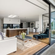 There is an easy flow between interior and apartment, architecture, building, ceiling, coffee table, daylighting, design, door, floor, flooring, furniture, hardwood, home, house, interior design, laminate flooring, living room, loft, property, real estate, room, table, wall, window, wood flooring, white, gray