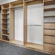 The walk-in wardrobe features comprehensive built in wood