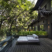 This seating area is surrounded by trees - architecture, backyard, cottage, courtyard, deck, estate, home, house, outdoor structure, plant, property, real estate, residential area, tree, walkway, black, brown