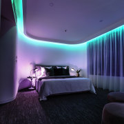 Considering the apartment was originally built in the architecture, ceiling, hotel, interior design, light, lighting, purple, room, suite, wall, black, blue