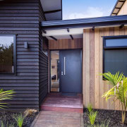 The front of this Waitoki home - Entrance architecture, backyard, cottage, door, facade, home, house, property, real estate, residential area, siding, window, gray
