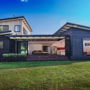 A wide shot of the entire Waitoki home cottage, elevation, estate, facade, home, house, property, real estate, residential area, siding, blue