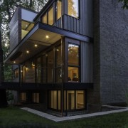 The home appears to rise up out of architecture, cottage, facade, home, house, property, real estate, siding, window, black