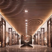Wood slats run along the ceiling, with wave architecture, ceiling, interior design, lighting, lobby, structure, symmetry, brown