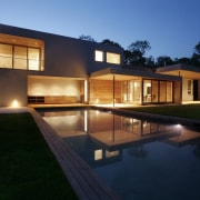 The pool runs right up to the home architecture, backyard, estate, facade, home, house, landscape lighting, lighting, property, real estate, reflection, residential area, siding, swimming pool, window, black