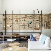 This large shelving unit doesn't seem to intrude furniture, home, interior design, living room, shelf, shelving, wall, white