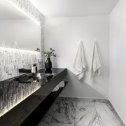 The illuminated mirror is the stand-out element in apartment, architecture, bathroom, black and white, ceiling, daylighting, design, floor, home, house, interior design, monochrome, monochrome photography, product design, room, tap, white, gray
