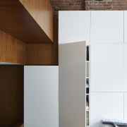Storage abounds along this wall of the living architecture, floor, interior design, plywood, product design, wall, wood, white, brown
