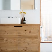 The timber continues into the bathroom. - The bathroom, bathroom accessory, bathroom cabinet, cabinetry, chest of drawers, countertop, drawer, floor, furniture, kitchen, product design, sideboard, sink, tap, wood, white