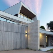 The exterior features concrete, wood, rock and glass architecture, building, elevation, facade, home, house, property, real estate, residential area, siding, gray