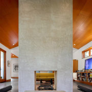 A fireplace, with a chimney rising up to architecture, ceiling, daylighting, fireplace, floor, hearth, interior design, living room, table, wall, gray, brown