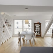 The dining room sits between two building support architecture, ceiling, dining room, floor, flooring, home, house, interior design, interior designer, living room, loft, room, table, wall, wood flooring, gray