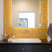 The yellow certainly draws the eye in this bathroom, floor, flooring, interior design, room, sink, tile, wall, window, orange, black