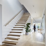The floating staircase rises up the first floor architecture, daylighting, floor, flooring, handrail, hardwood, home, house, interior design, laminate flooring, real estate, stairs, wood, wood flooring, gray, white