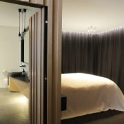 This underlit vanity continues the 'folding' motif found bed, bedroom, furniture, interior design, lighting, room, suite, gray, black