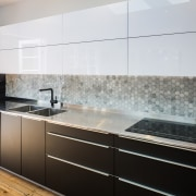 Hexagonal tiles make up the long splashback cabinetry, countertop, floor, interior design, kitchen, product design, gray, black, white