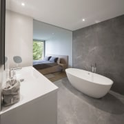 The walls and floor and frame this freestanding architecture, bathroom, bidet, floor, interior design, product design, real estate, room, sink, tap, tile, gray