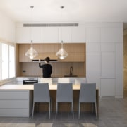 The kitchen features a low island at an architecture, cabinetry, countertop, cuisine classique, floor, flooring, interior design, kitchen, real estate, room, tile, wood flooring, white, gray