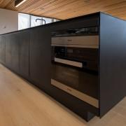 The main black surface is viewed on entering floor, flooring, furniture, hardwood, table, wood, black, brown