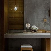 A concrete vanity is lit by a single architecture, bathroom, floor, flooring, furniture, interior design, product design, sink, tile, wall, wood, black, brown