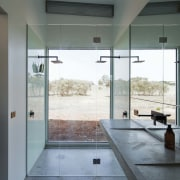 The double shower lacks privacy, but makes up architecture, bathroom, door, floor, flooring, glass, house, interior design, plumbing fixture, room, tile, gray