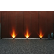 The lights on this weathering steel wall give fireplace, hearth, heat, red, white