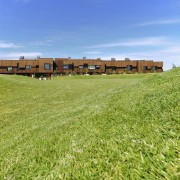 The development almost blends into the environment thanks estate, farm, field, grass, grass family, grassland, house, land lot, lawn, meadow, pasture, plain, prairie, property, real estate, residential area, rural area, sky, green, teal