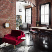 A brick archway gives the feeling of an chair, floor, flooring, furniture, home, interior design, living room, loft, table, window, black, red
