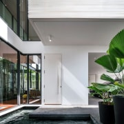 The living area opens up to the inner architecture, condominium, courtyard, daylighting, facade, home, house, interior design, property, real estate, white, gray