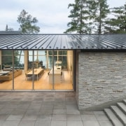 The driveway leads you down to the glass-covered facade, home, house, property, real estate, roof, shed, gray