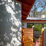 A wood soffit and gate to the courtyard home, house, outdoor structure, roof, shed, siding, wood, gray