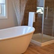 This freestanding tub makes the bathroom feel significantly bathroom, bathtub, floor, flooring, interior design, plumbing fixture, room, tile, brown, gray