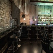 While less exaggerated, the bar still features elements bar, café, interior design, restaurant, black