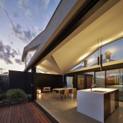 Another view of the home at dusk - architecture, ceiling, daylighting, home, house, interior design, lighting, real estate, roof, brown