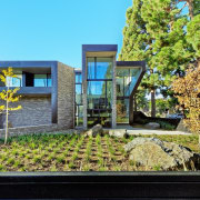 Simple, low maintenance gardens run around the outside architecture, cottage, facade, home, house, neighbourhood, property, real estate, residential area, tree