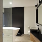 A freestanding tub and a floor-to-ceiling glass shower architecture, bathroom, floor, flooring, interior design, plumbing fixture, room, sink, tap, tile, wall, gray