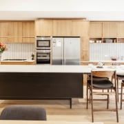 Wood cabinets and an elevated island help to cabinetry, countertop, cuisine classique, furniture, interior design, kitchen, product design, table, white