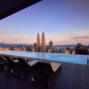 Infinity pools offer unparalleled luxury - Infinity pools architecture, building, city, cityscape, condominium, downtown, dusk, evening, horizon, hotel, real estate, reflection, roof, sea, sky, skyline, skyscraper, sunset, water, purple, blue