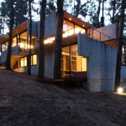 The home is nestled among the surround pine architecture, cottage, home, house, log cabin, property, real estate, black