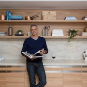 Josh Emett next to his SCE Stone & furniture, kitchen, shelf, shelving, gray, brown