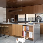 The shelf unit in this waterfall island is architecture, floor, flooring, furniture, interior design, kitchen, table, brown, gray