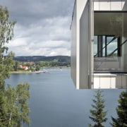 The house hangs out over the reservoir - architecture, building, cloud, facade, home, house, real estate, reflection, sky, water, window, gray